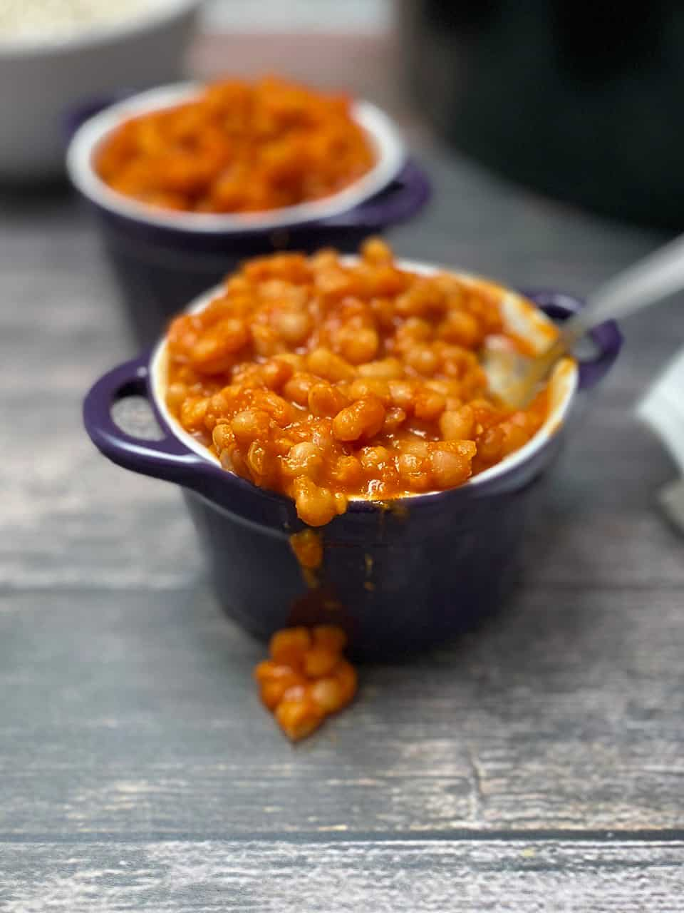 spoon inside purple bowl filled with saucy baked beans