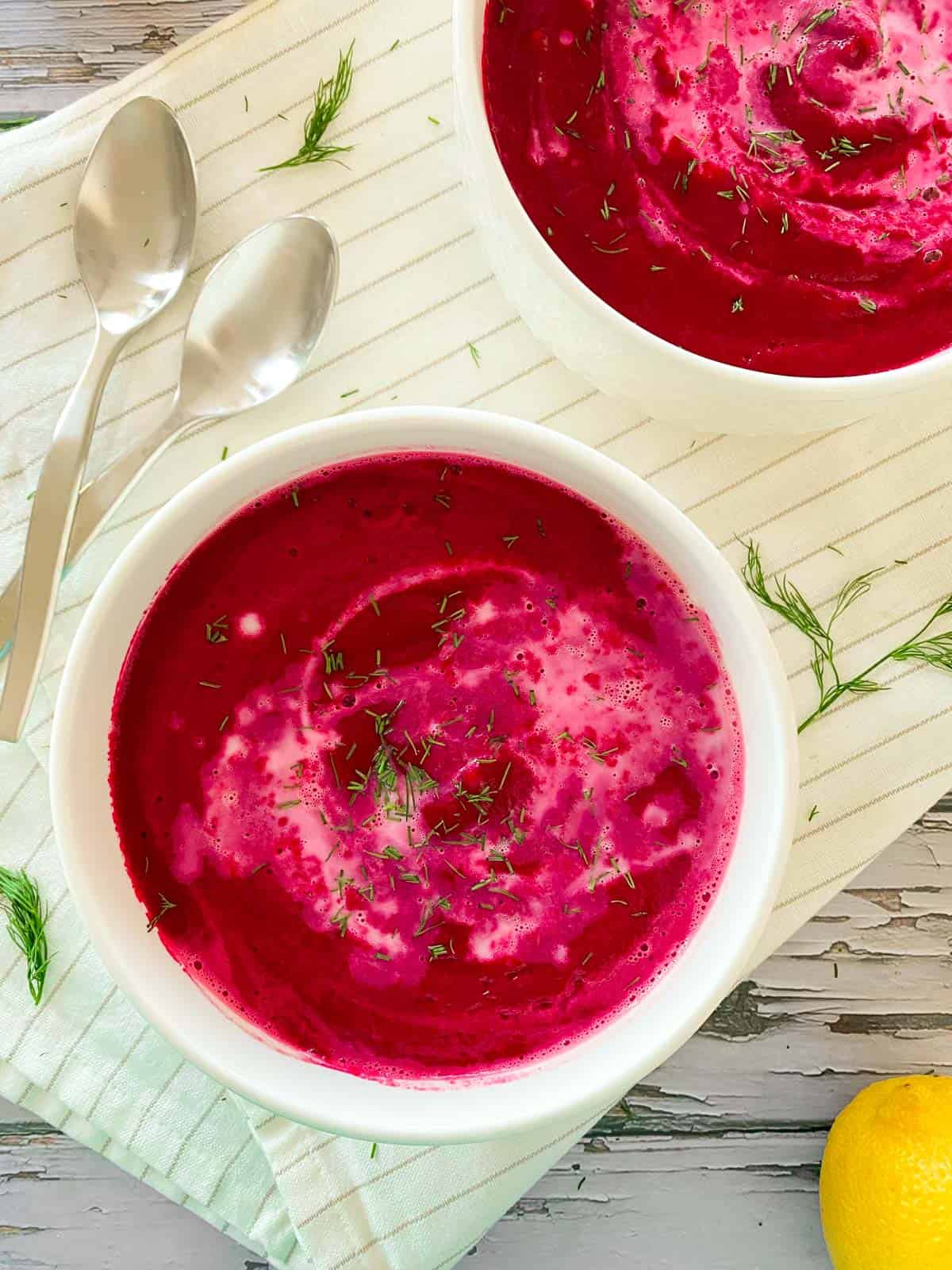 Two bowls filled with red soup with fresh dill on top.
