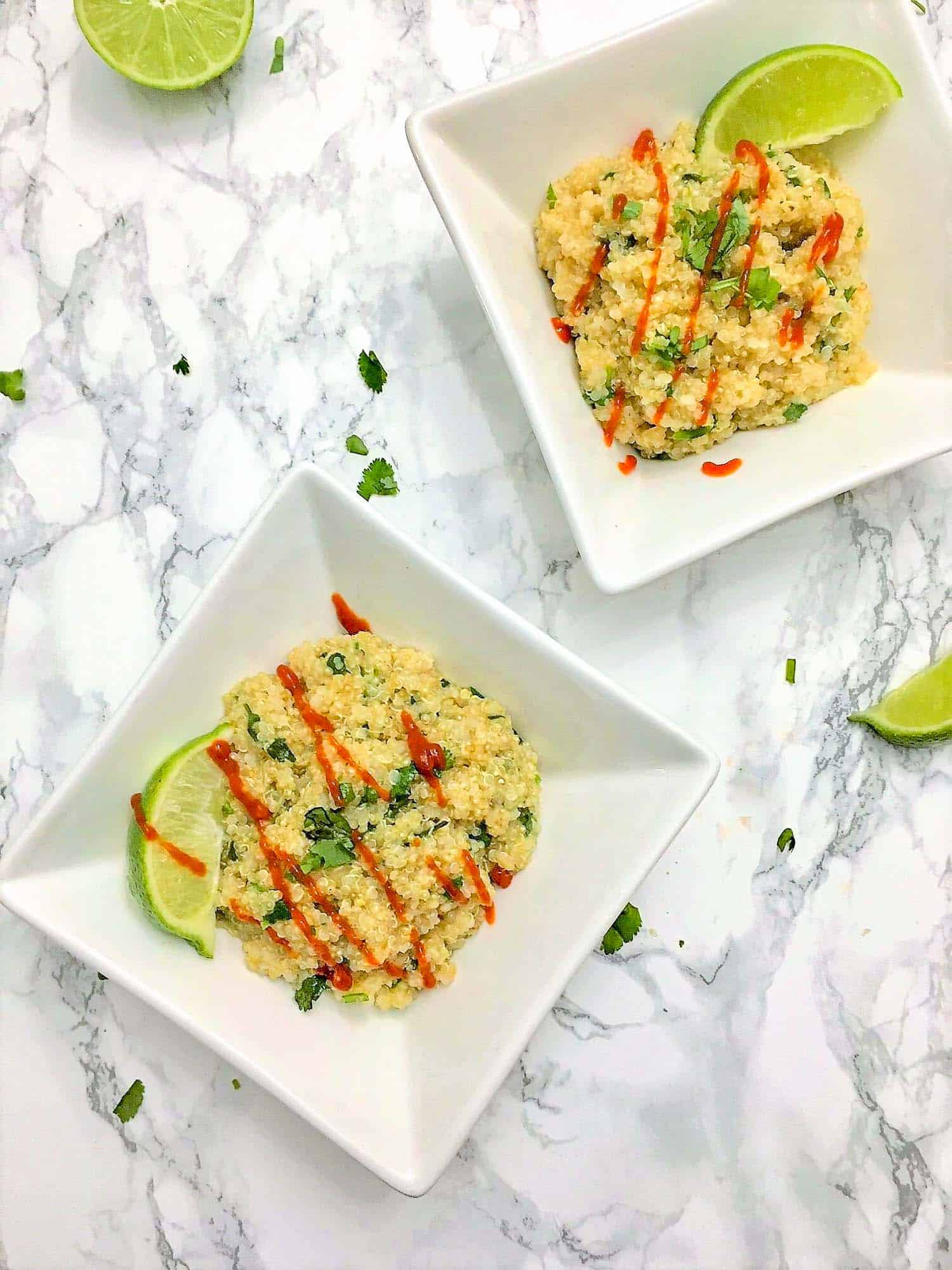 cooked quinoa in square dish with lime wedge and hot sauce drizzled on top