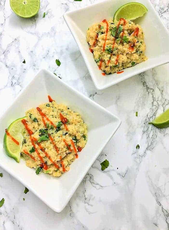 quinoa in 2 square bowls with hot sauce and lime wedges on top
