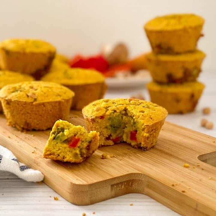 vegan savoury muffin with triangular piece cut out on cutting board.