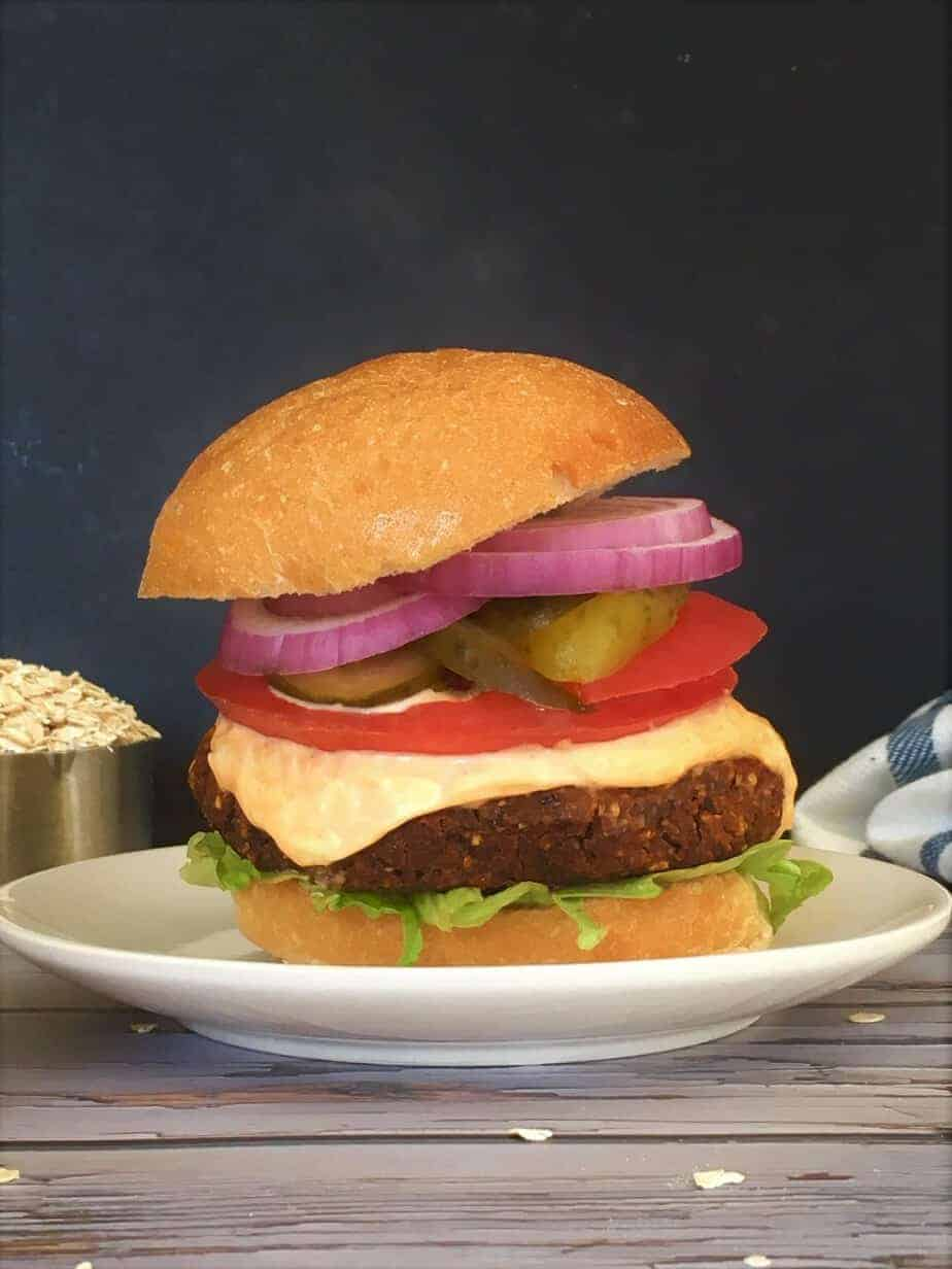 burger in bun with tomato, onion, pickle, spicy mayo