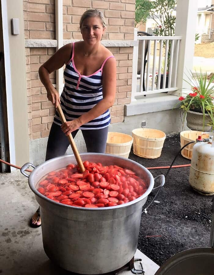 stirring large pot of tomatos