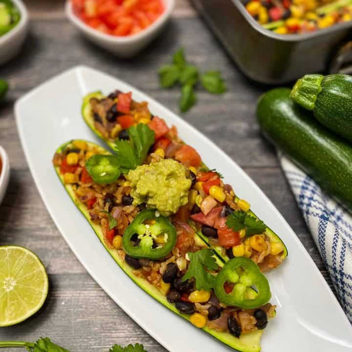 2 burrito stuffed zucchini boats on white plate