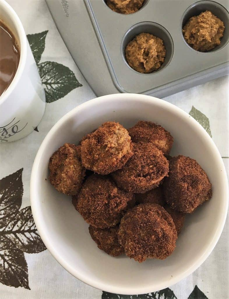 pumpkin spice donut holes in bowl with coffee
