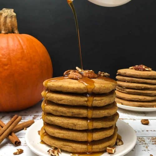 stack of pumpkin spice pancakes in plate with pumpkin in background