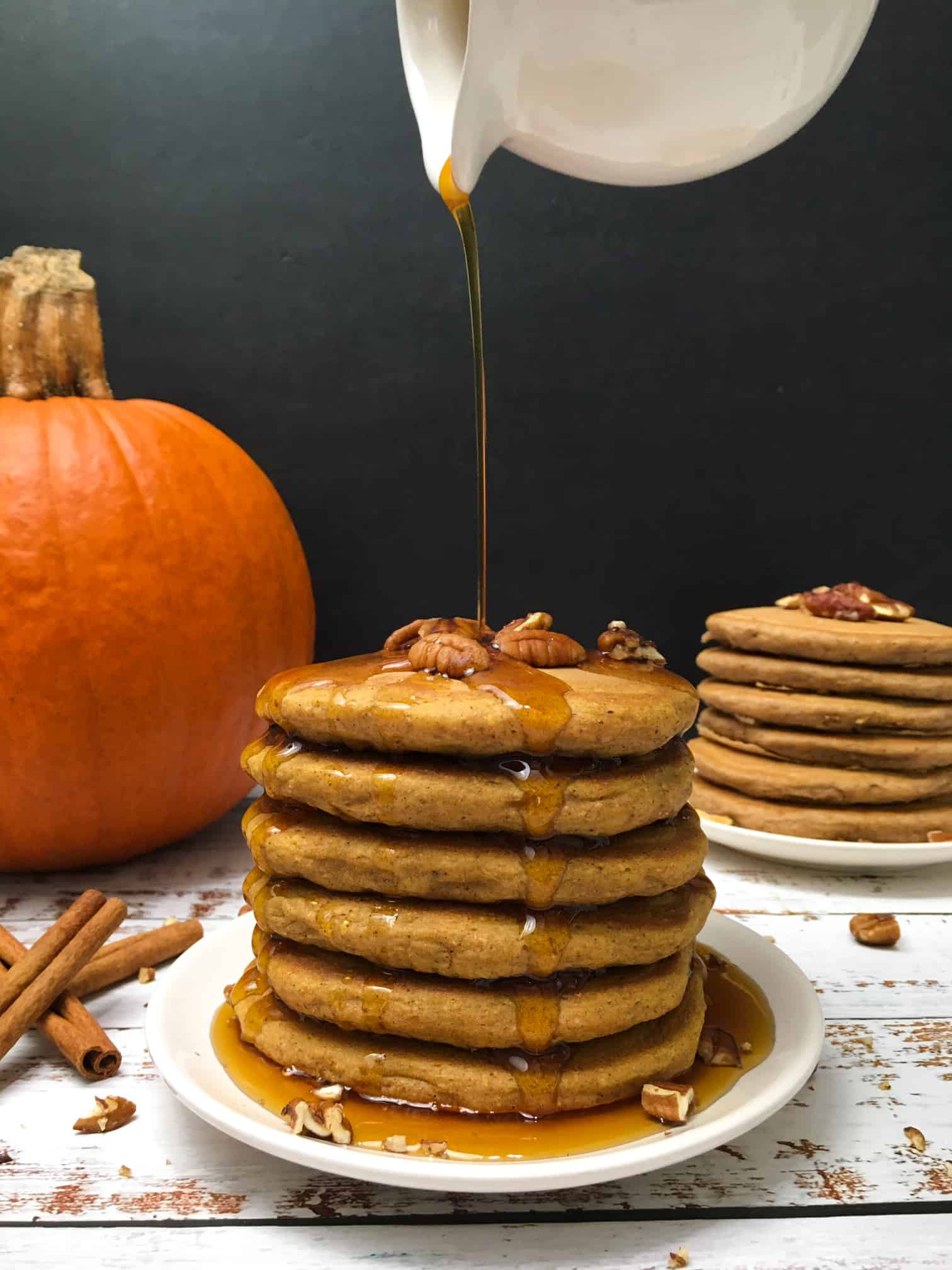 syrup drizzling over stack of pumpkin spice pancakes.