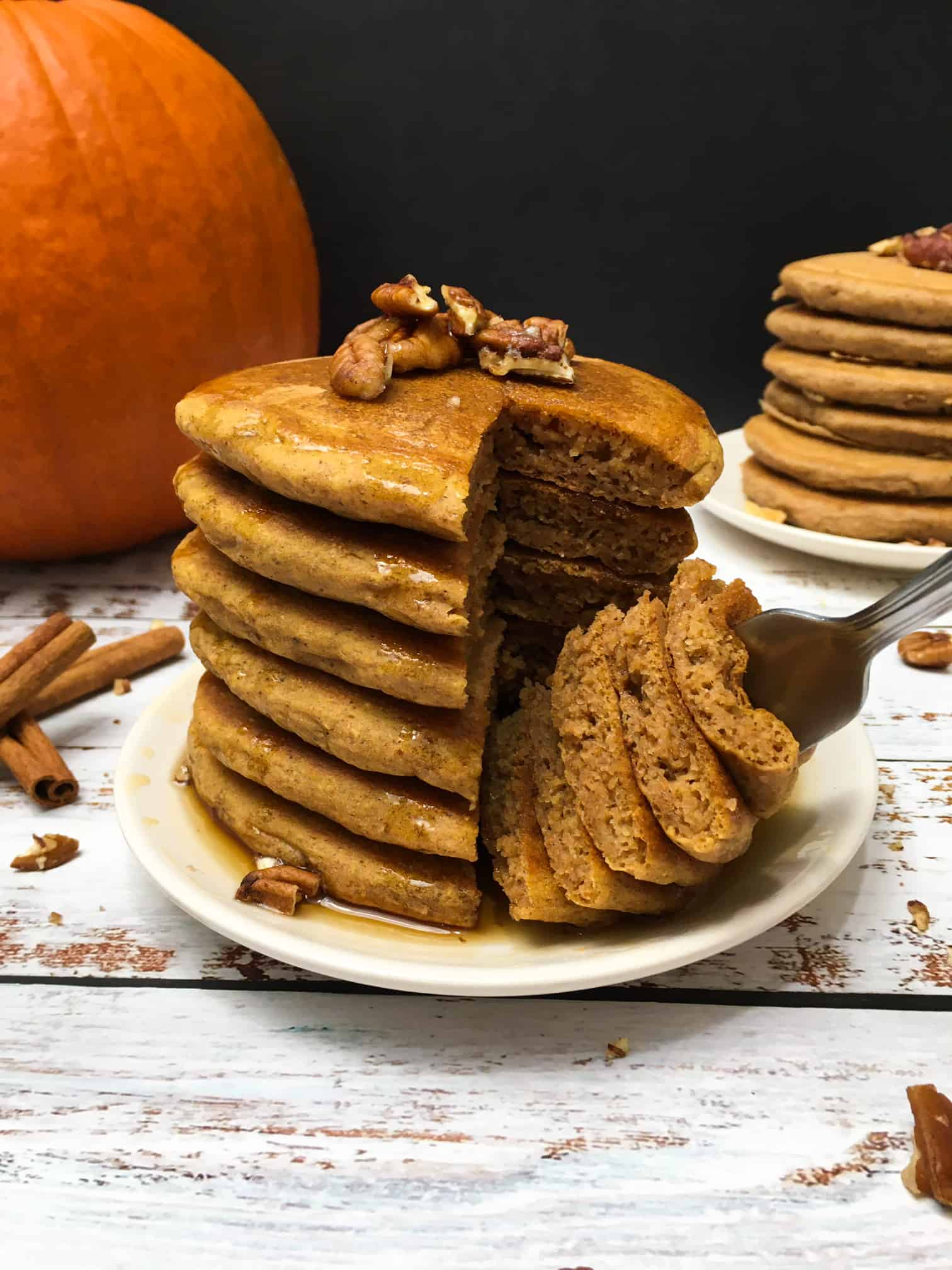 fork cutting through stack of pumpkin spice pancakes.