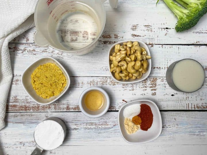 bowls of cashews, nutritional yeast, vinegar, spices, flour, milk, and water