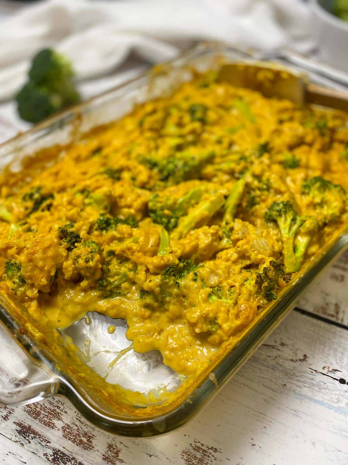 creamy casserole with broccoli in glass dish with a section missing from tray