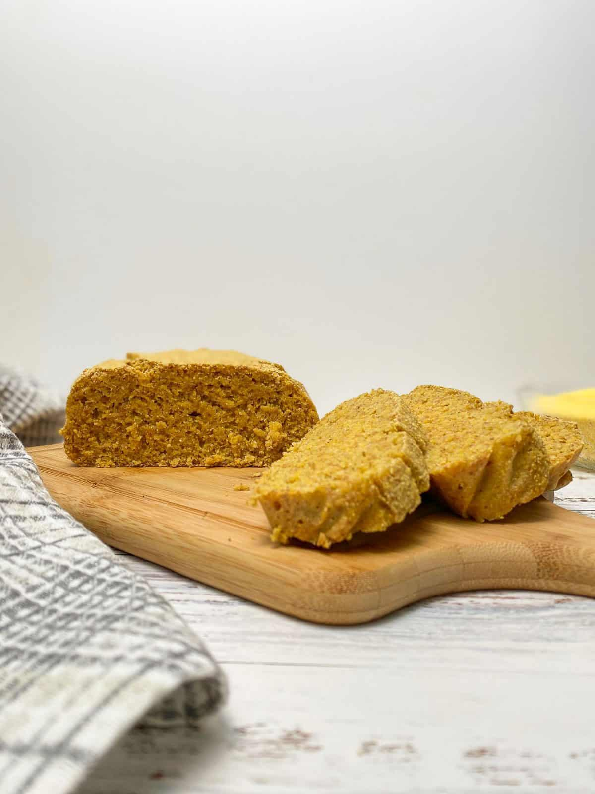 loaf of cornbread on wooden cutting board with 3 slices cut