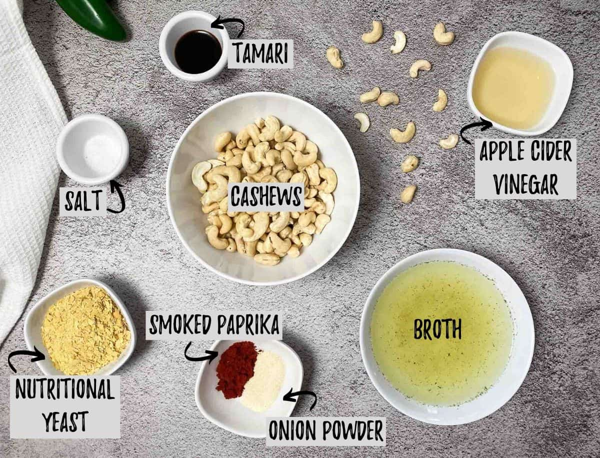 ingredients to make vegan cheese sauce: cashews, broth, seasoning, nutritional yeast, vinegar and tamari