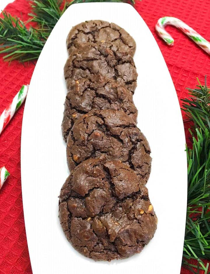 chocolate brownie cookies in white tray with candy canes in background