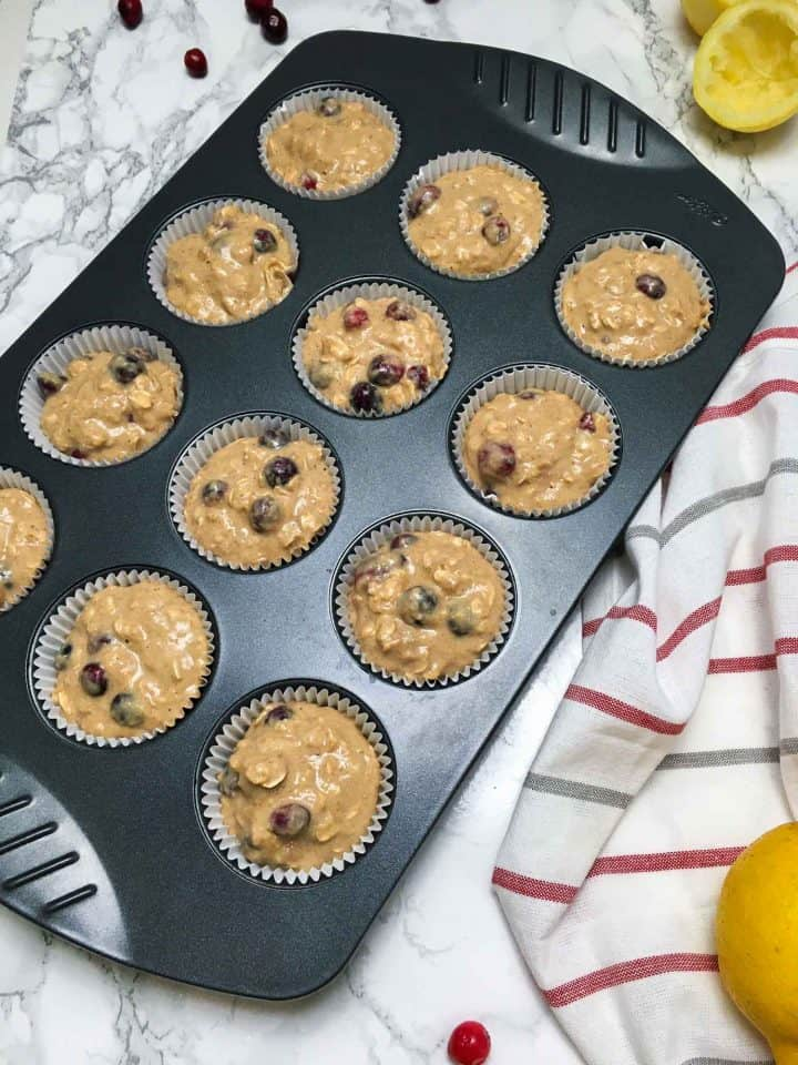 muffin pan filled with lemon cranberry muffin batter