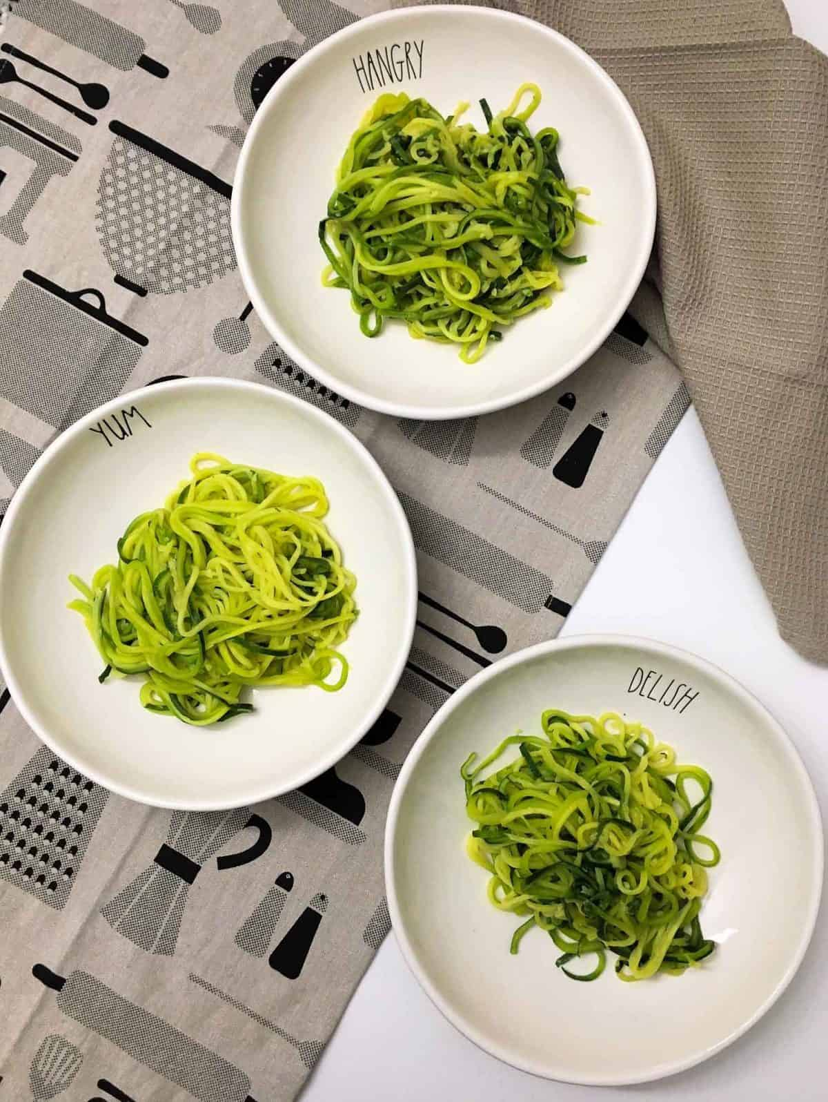 three plates of zucchini noodles cooked