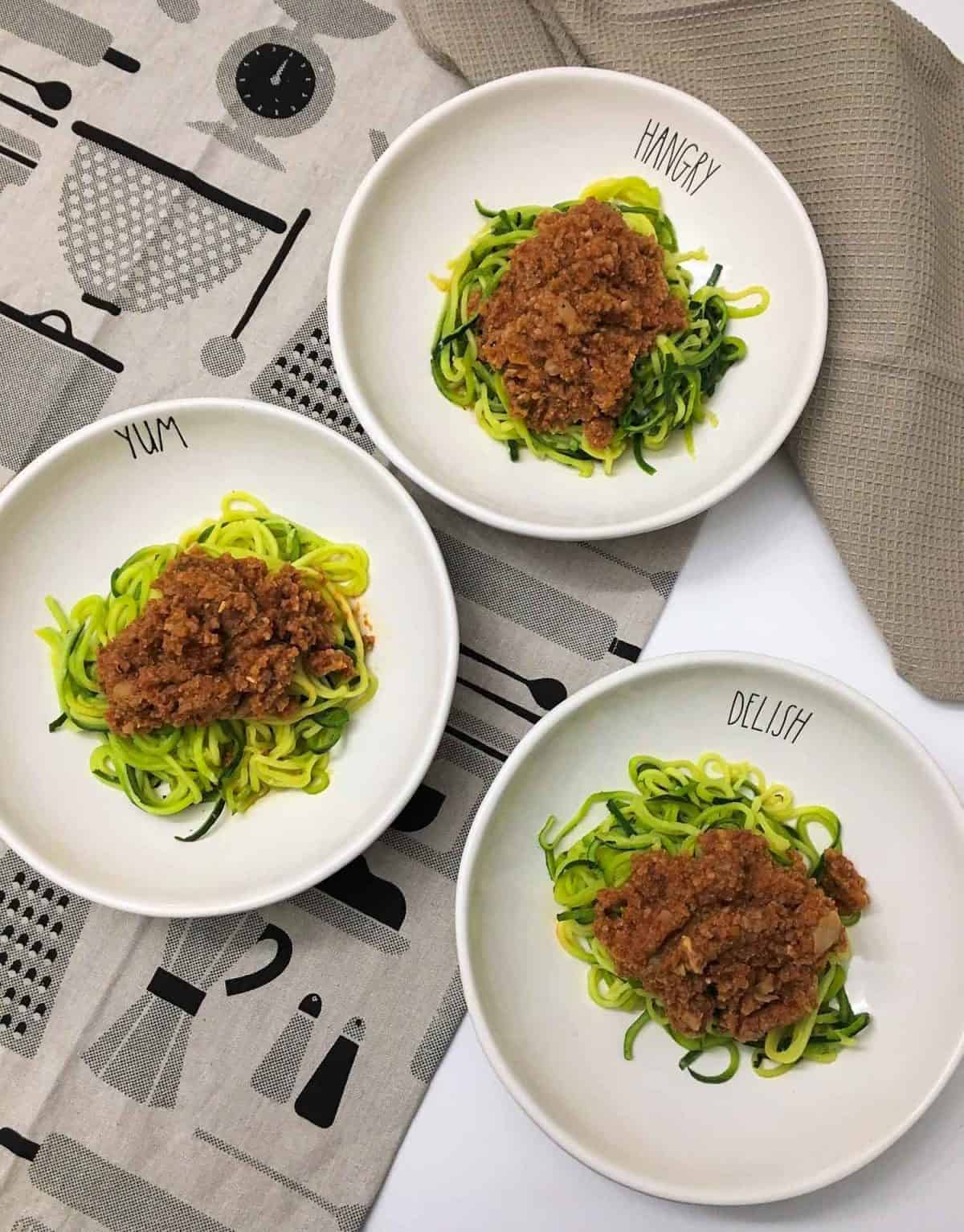 three plates of zucchini noodles with bolognese sauce on top