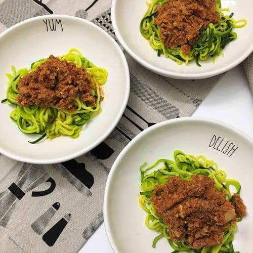 plates of zoodles with vegan bolognese sauce
