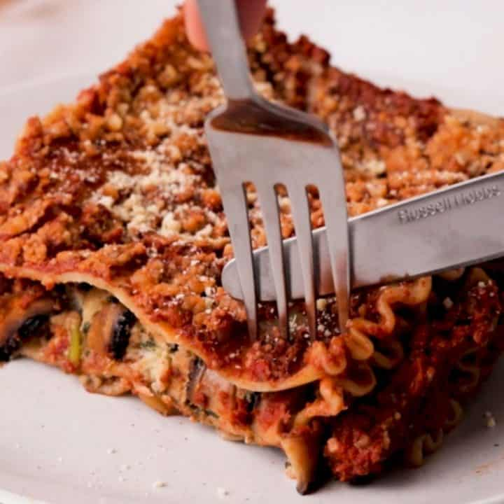 Fork and knife cutting into slice of vegan lasagna.