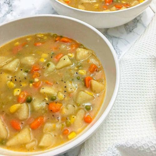 bowl of vegetable soup with potatoes, corn, peas, carrots
