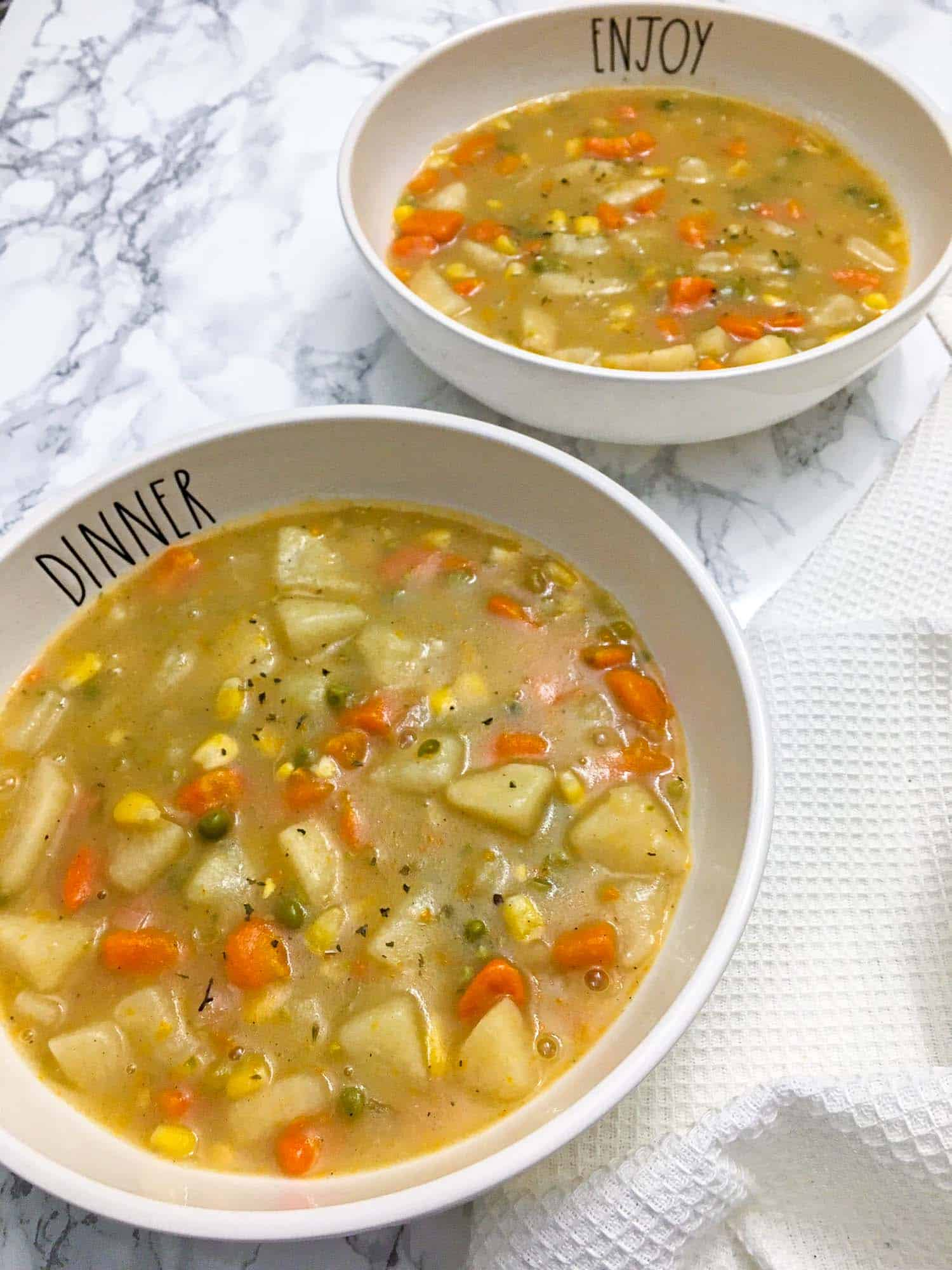 two bowls of vegetable soup on marble counter