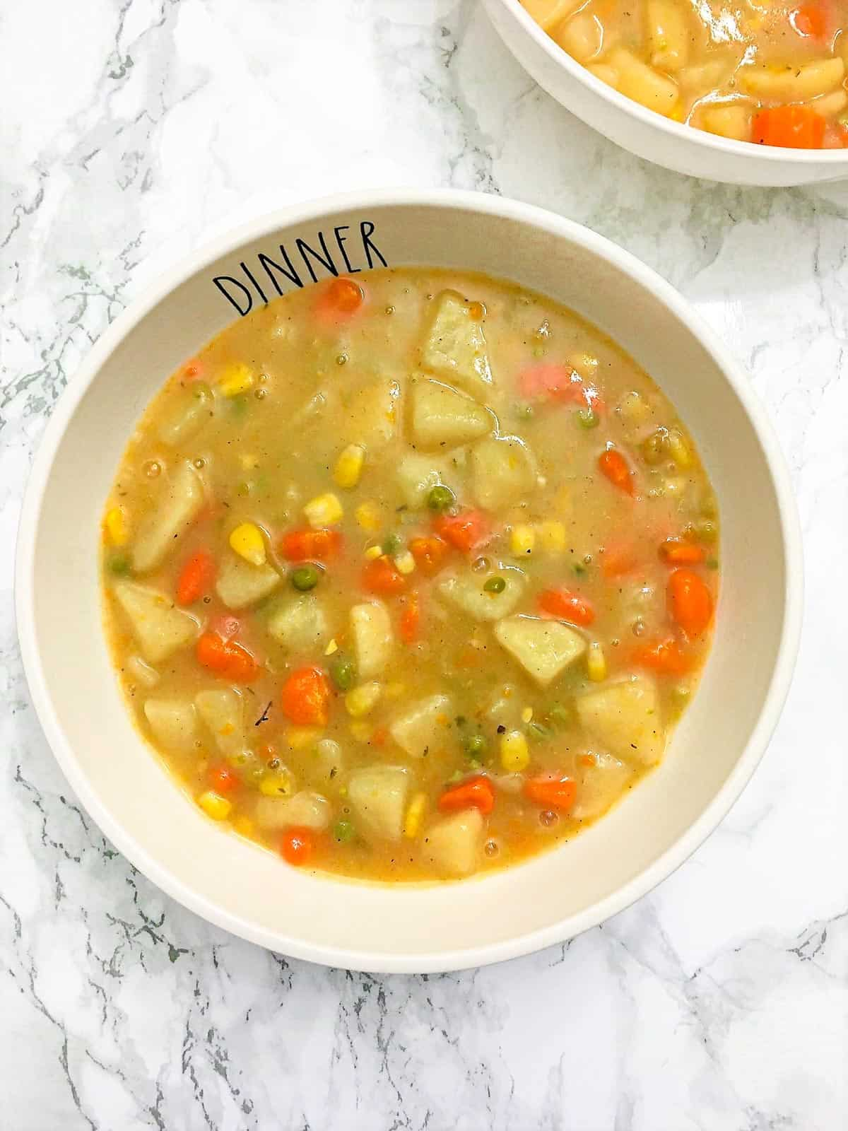Bowl of soup with potatoes, carrots, corn, peas in bowl that has text spelling dinner.