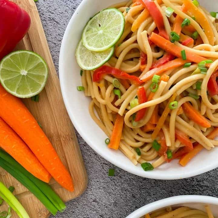 White bowl of noodles, carrots and peppers with lime wedge garnish.