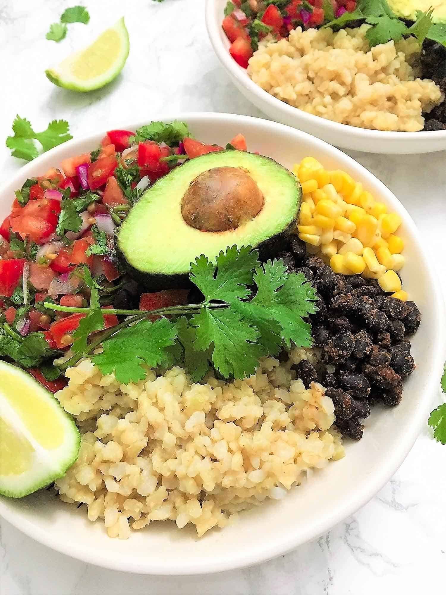 rounded mexican buddha bowl of rice, black beans, corn, tomato salad, avocado and a lime wedge