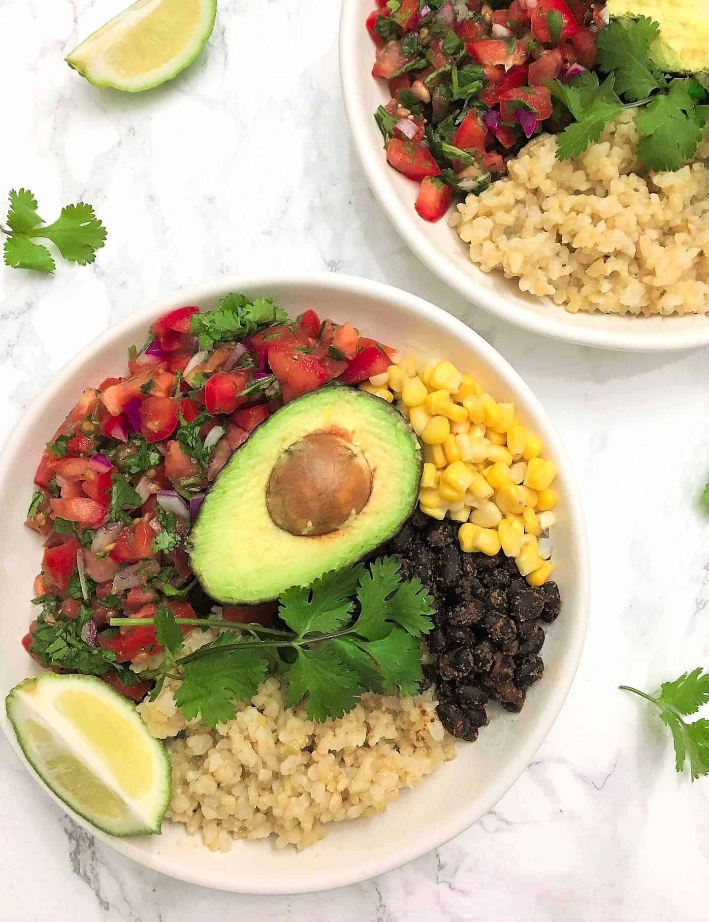 Two bowls with rice, tomato salad, corn, black beans, avocado and lime.