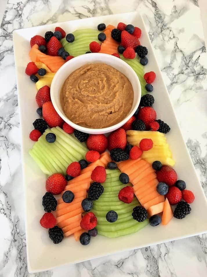 Sweet hummus fruit dip in a bowl on the center of a platter surrounded by fresh fruit