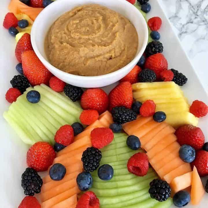 Sweet hummus fruit dip in center of a platter of fresh fruit