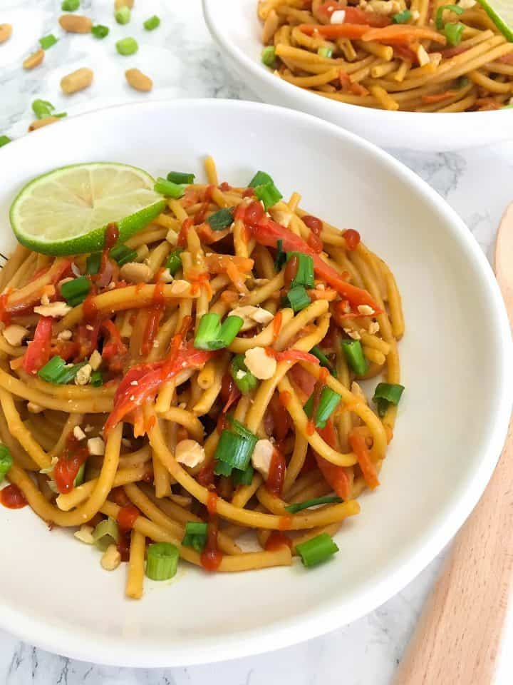 Thai Peanut Noodles in bowls garnished with lime, peanuts, green onion, hot sauce