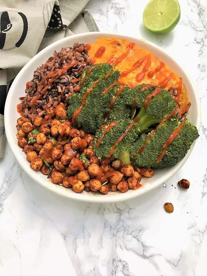 chili lime chickpea buddha bowll with broccoli, sweet potato, wild rice blend, and drizzled in sriracha sauce