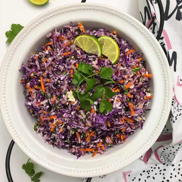 Coleslaw Salad with Thai Peanut Dressing in serving bowl with lime wedges and cilantro scattered