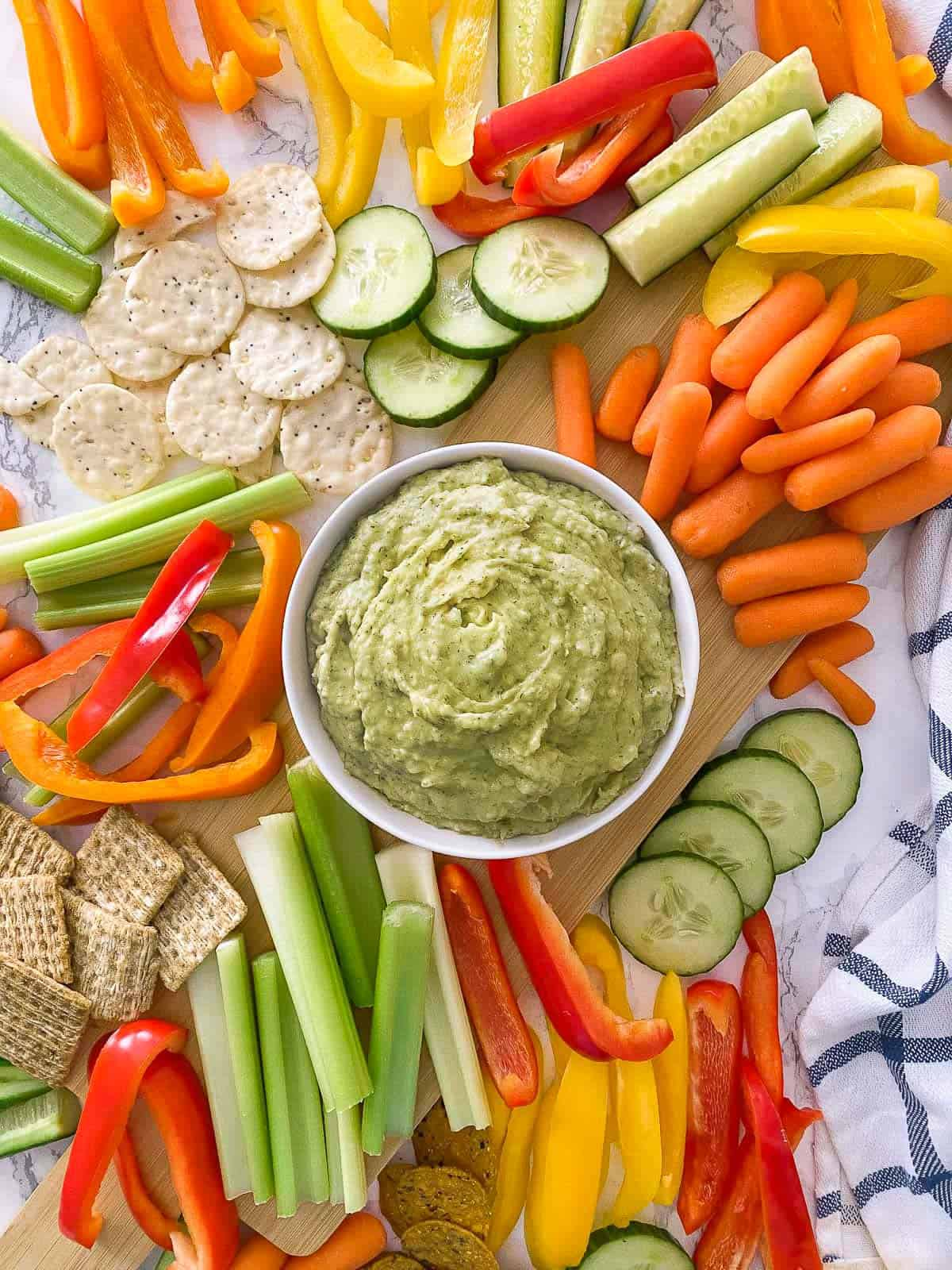 Bowl of green dip with carrots, cucumber, celery, bell peppers and crackers around it.