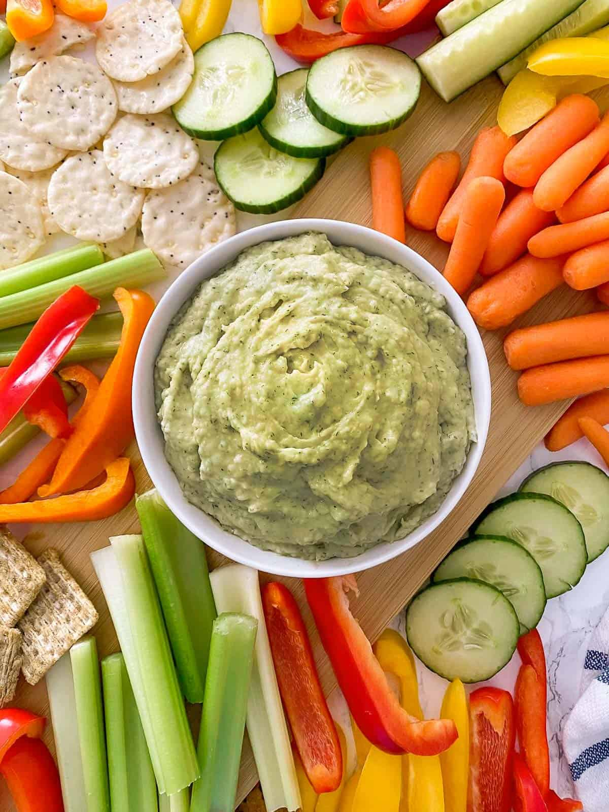 Bowl of dill pickle hummus on cutting board, surrounded by raw veggies.