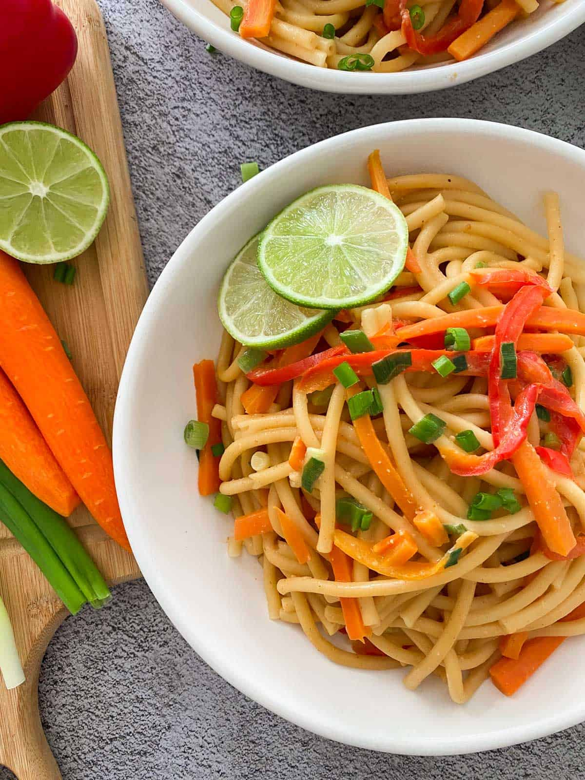 spicy thai noodles in bowl with carrots, red pepper and lime.