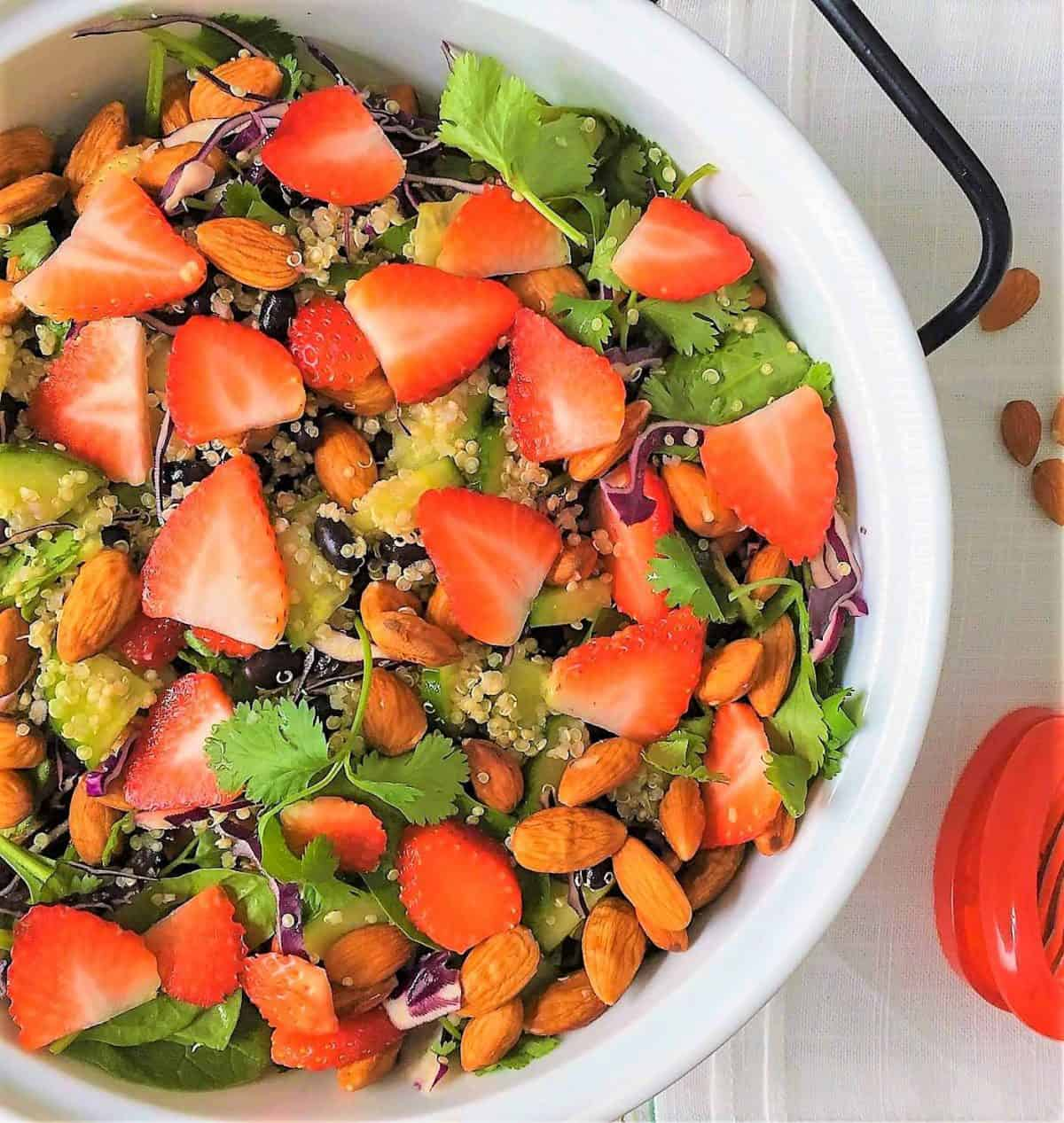 Strawberry Spinach Salad in serving bowl with scattered almonds