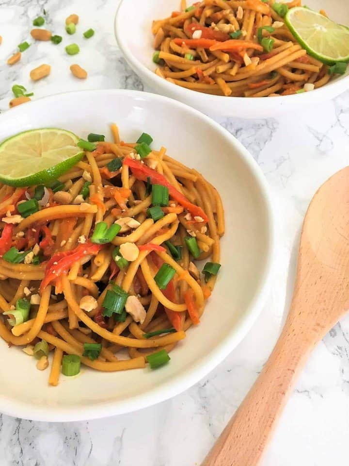 Thai Peanut Noodles in bowls garnished with lime, peanuts, green onion
