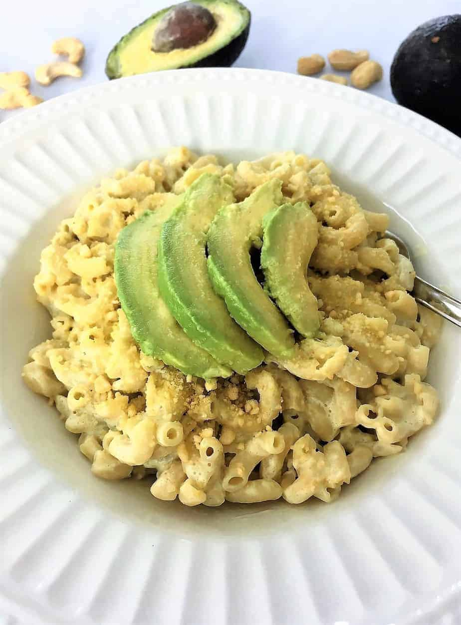 avocado mac and cheese in bowl close up with cashews scattered around the bowl