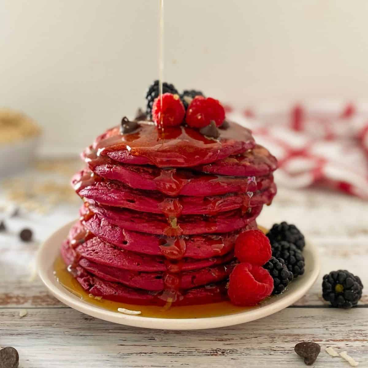 pink pancakes stacked on white plate with syrup dripping down them.