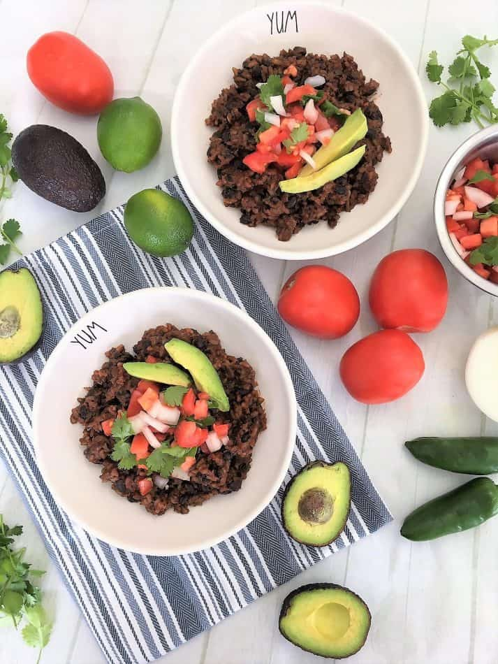 Instant Pot Mexican Casserole in bowls with avocado, tomato, cilantro, white onion, with limes and jalapeno around bowls