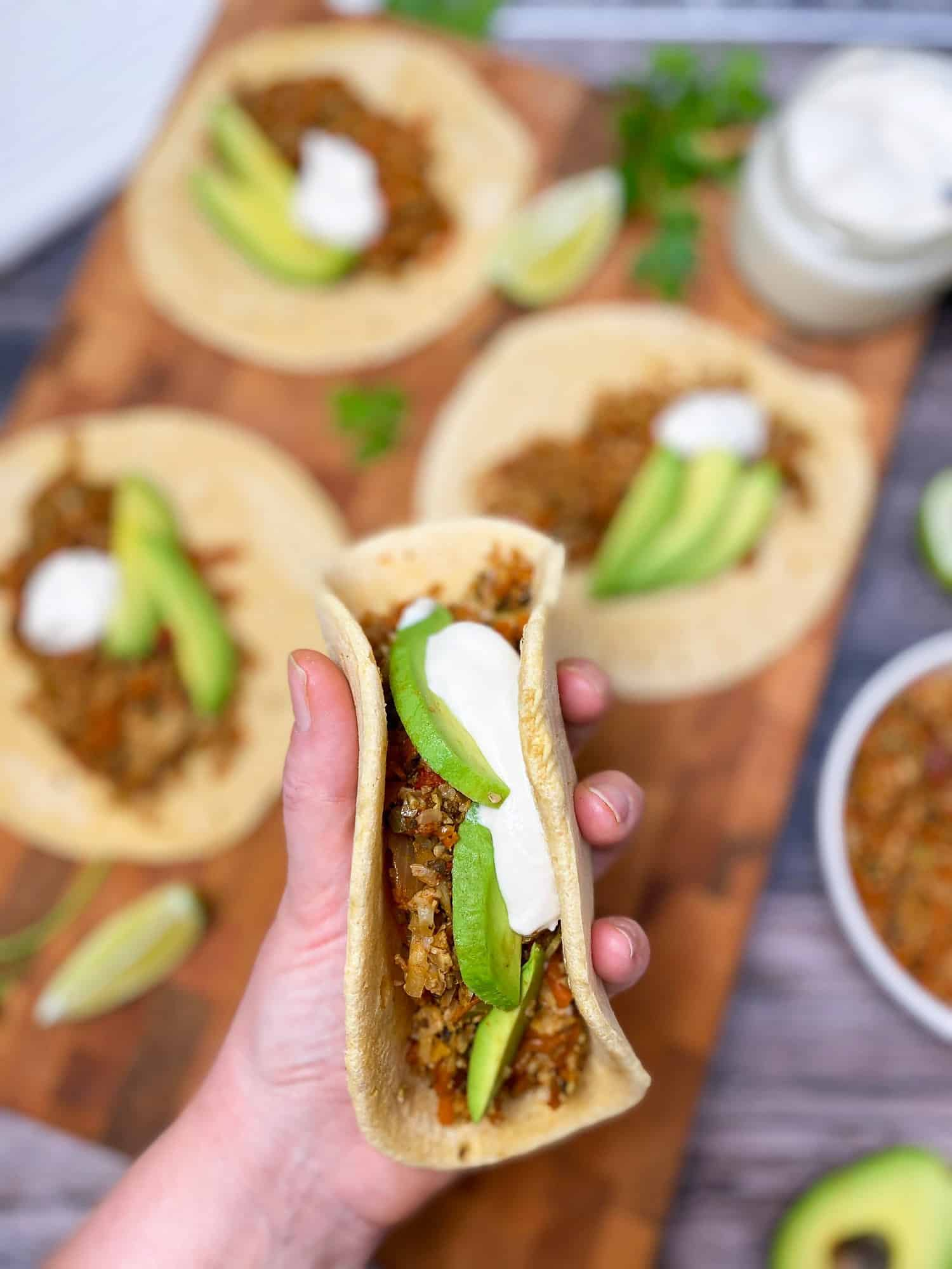 hand holding up a soft taco filled with ground veggies, avocado and sour cream