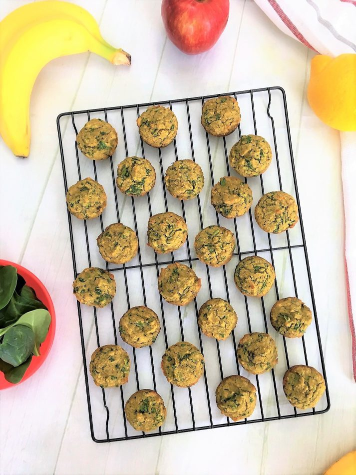 banana spinach muffin bites on cooling rack with banana, apple, lemon, spinach in background