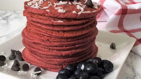 beet pancakes stacked on plate with blueberries, shredded coconut, chocolate chips