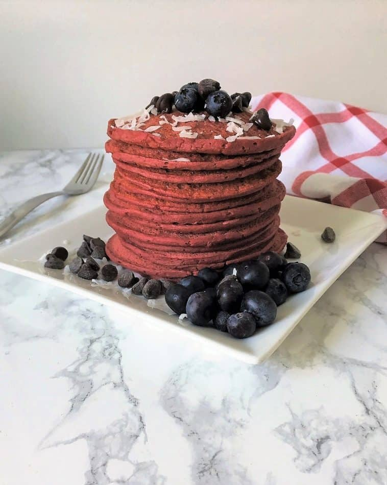beet pancakes stacked on a plate with berries and coconut flakes