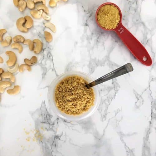 vegan parmesan cheese with cashews spilled and nutritional yeast in measuring spoon