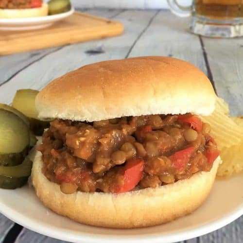 vegan sloppy joes in gluten free bun on a plate with pickles and chips