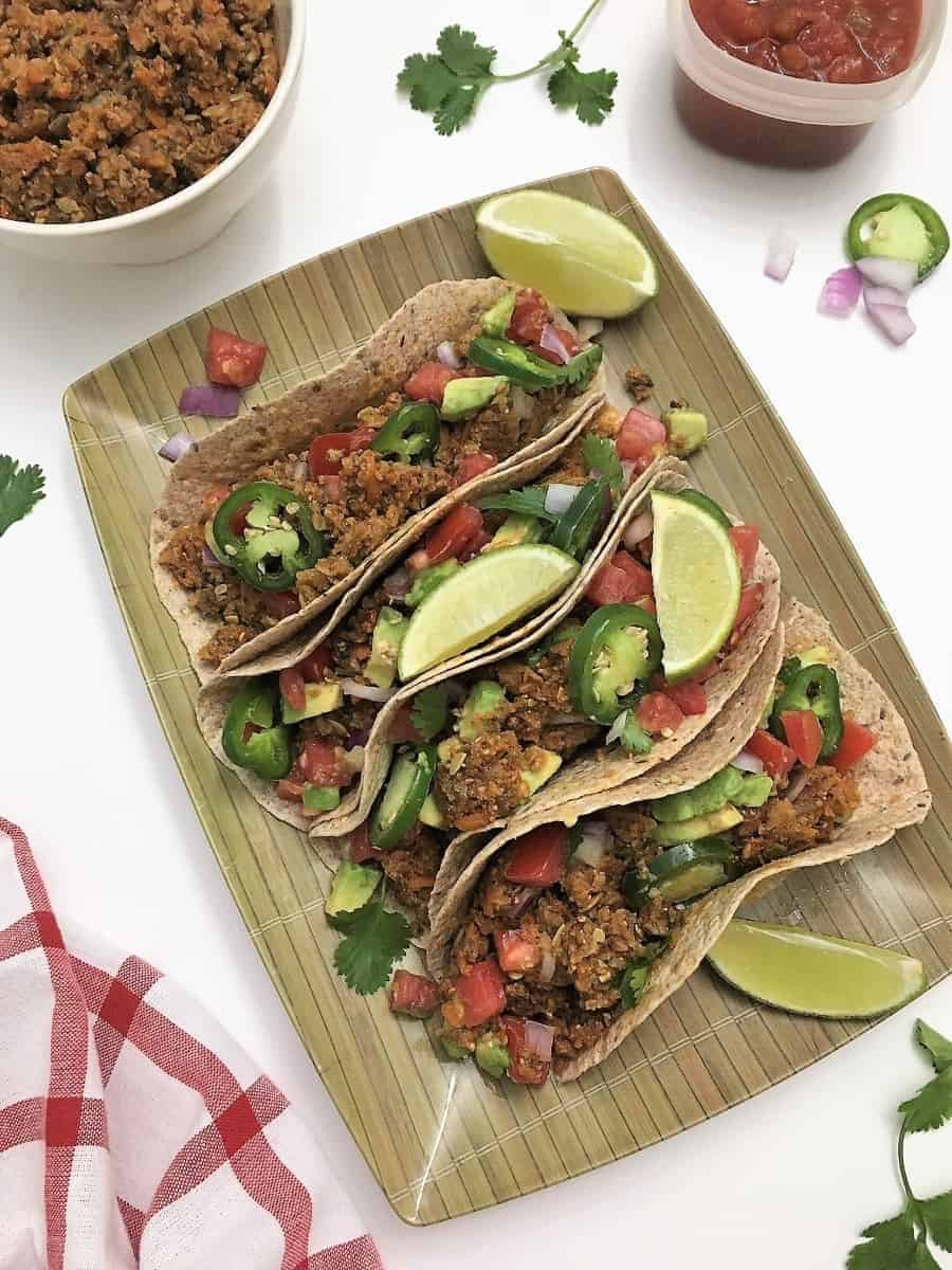 four tortillas on a platter with vegan taco meat, tomato, cilantro, jalapeno, and lime wedges