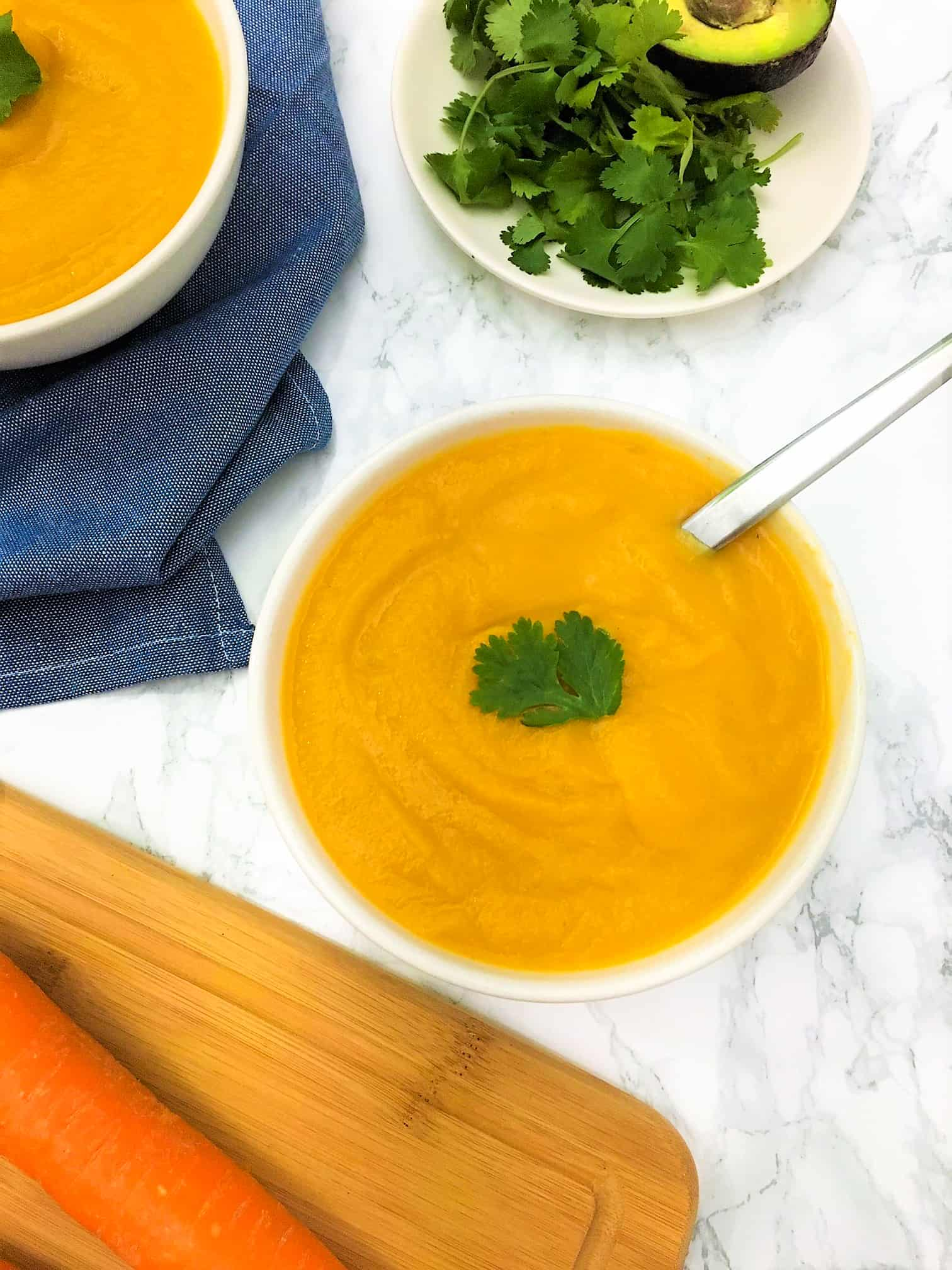 carrot cauliflower soup in bowl with sage and spoon