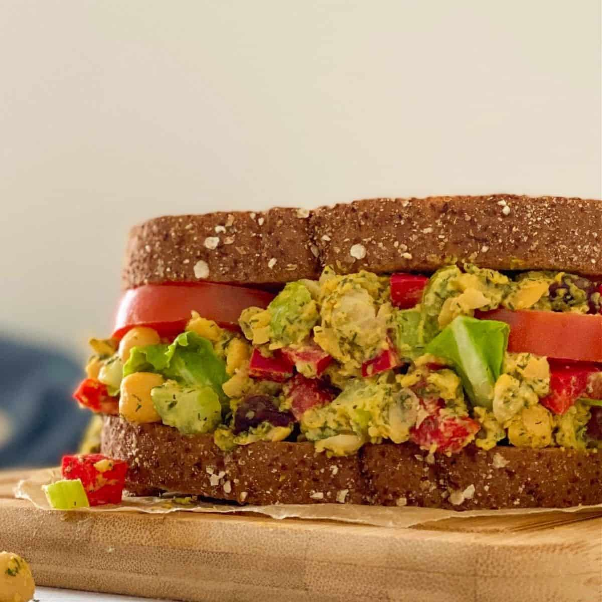 Sandwich resting on cutting board with chickpeas, tomato, celery, peppers and dill.